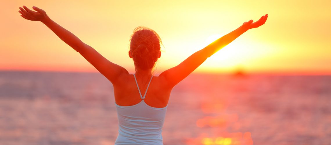 Rear view of young woman raising arms at sunset. She is in sports clothing. Female is enjoying view at beach.